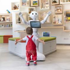 Un enfant ouvrant les bras au robot Pepper à l'Office de tourisme de Hauterives (Porte de Drôme Ardèche)