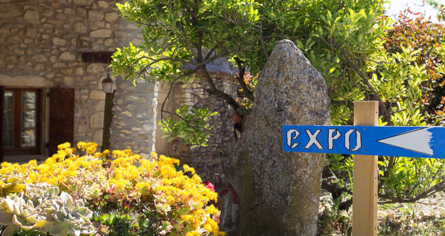 panneau indiquant expo devant une maison en pierres