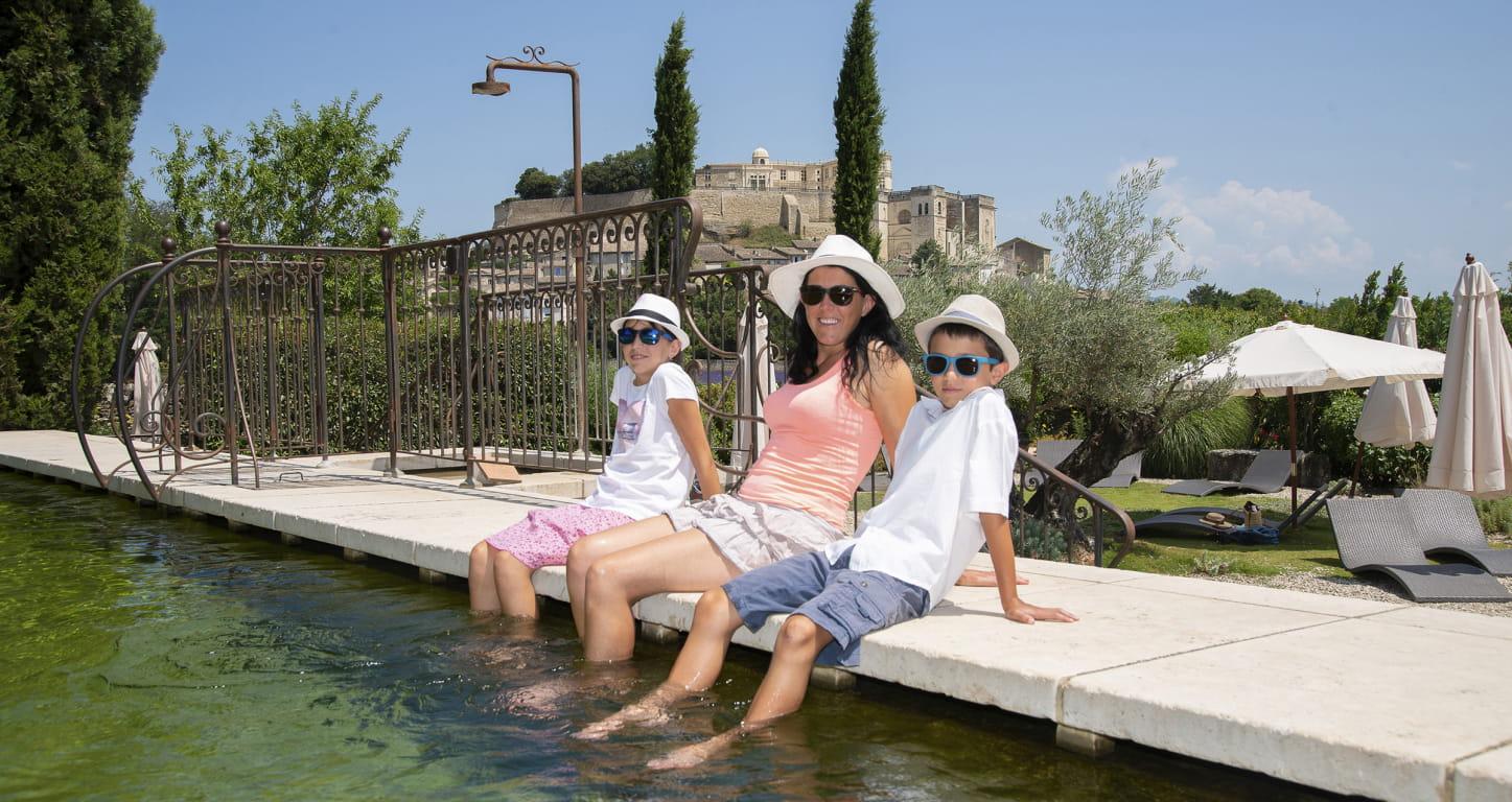 Famille les pieds dans l'eau dans la piscine du clair de la Plume à Grignan