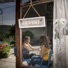deux jeunes femmes à la terrasse d'un café de village